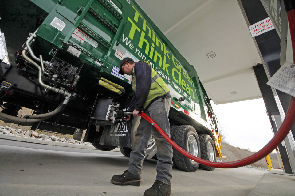 In this Nov. 19, 2012 photo, Waste Management driver Alan Sadler fills his truck with CNG gas at the company's filling station in Washington, Pa. Years from now, motorists needing a fill-up might see natural gas pumps sharing space at the neighborhood filling station with ones dispensing gasoline and diesel. (AP Photo/Gene J. Puskar)