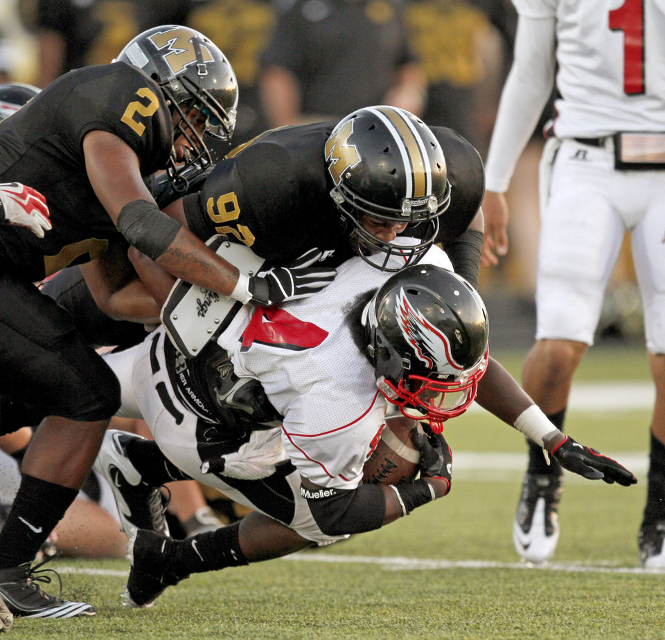 Midwest City's Myles Hogg, left, and Trevon Lewis bring down Del City's Adrian Fletcher during a high school football game in Midwest City, Okla., Friday, September 3, 2010.  Photo by Bryan Terry, The Oklahoman