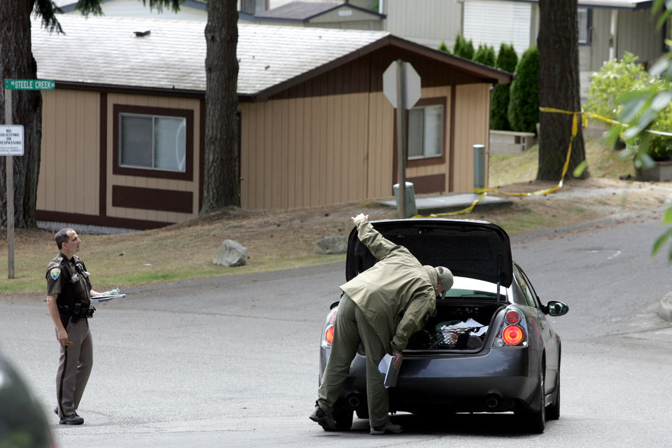 Photo - Law enforcement members search the trunk of a vehicle entering the Steele Creek Mobile Home Park on Tuesday, Aug. 5, 2014, in Bremerton, Wash. More than 100 officers from 10 law enforcement agencies are involved in the search for a 6-year-old girl who disappeared from her Washington state home over the weekend, sheriff's officials said Tuesday. Investigators don't know if the girl, Jenise Wright, wandered off or was the victim of an accident, abduction or homicide. (AP Photo/Kitsap Sun, Larry Steagall)