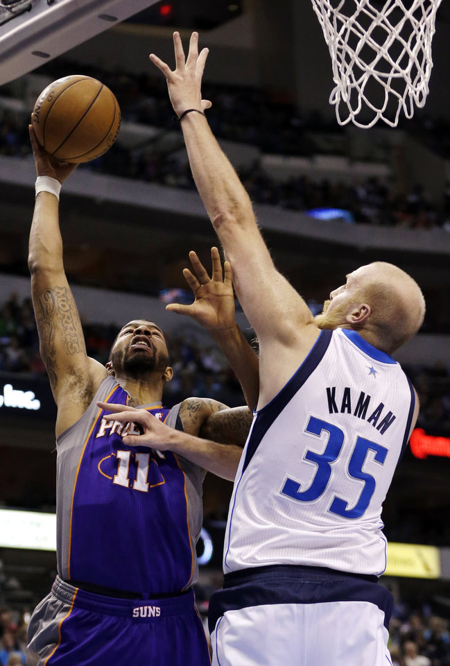 Photo - Phoenix Suns forward Markieff Morris (11) shoots against Dallas Mavericks center Chris Kaman (35) during the first half of an NBA basketball game, Wednesday, April 10, 2013, in Dallas. (AP Photo/LM Otero)