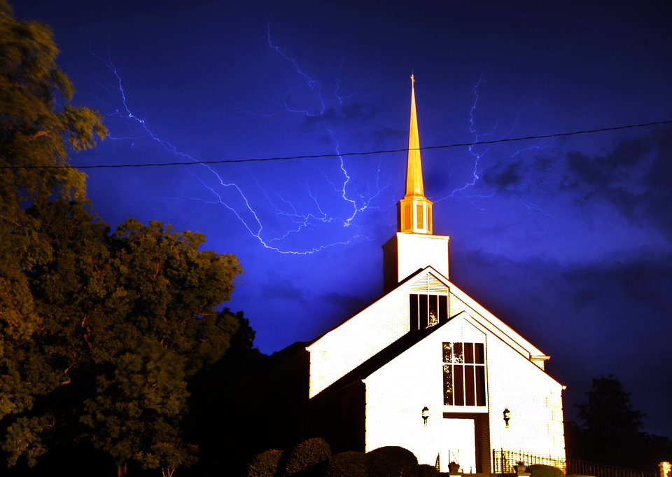Photo - Lightning streaks above Cornith Baptist Church in Athens, Ga., as a line of severe thunderstorms sweep across Georgia in the early morning on Thursday, April 28, 2011. At least 77 people have been killed in the outbreak severe weather across the south.  (AP Photo/ Athens Banner-Herald, David Manning)