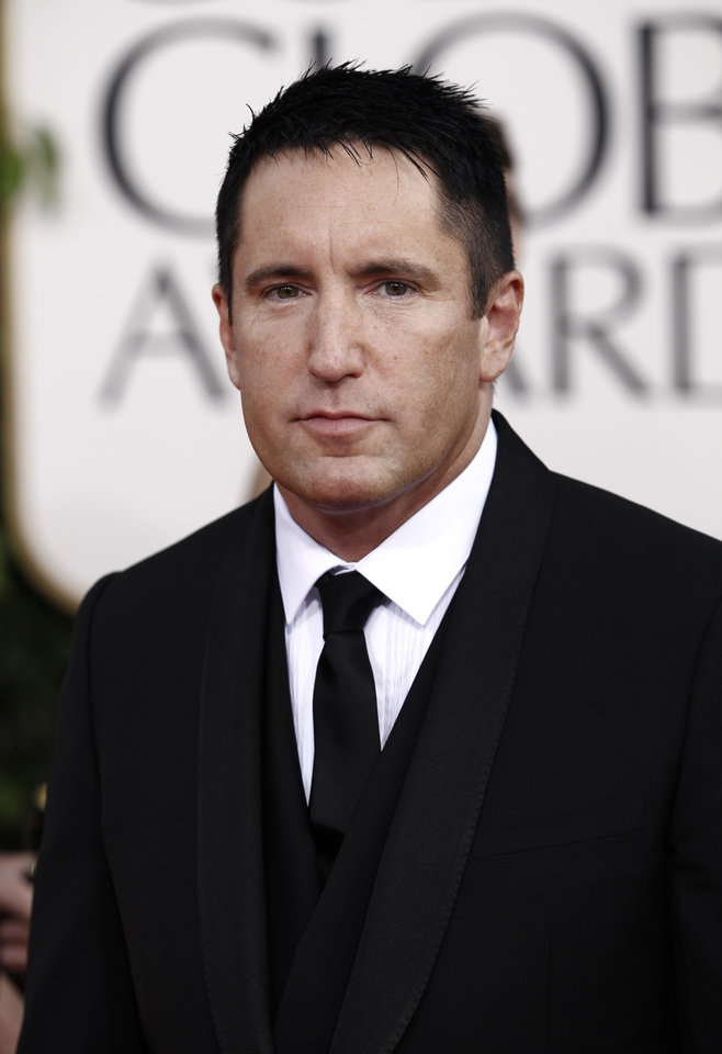 Photo - FILE - In this Jan. 16, 2011 file photo, Trent Reznor arrives for the Golden Globe Awards in Beverly Hills, Calif. Reznor and officials at Beats By Dre agree: Reznor is still with the company. Reznor tweeted Monday, June 2, 2014, that he remains the company's chief creative officer. (AP Photo/Matt Sayles, file)