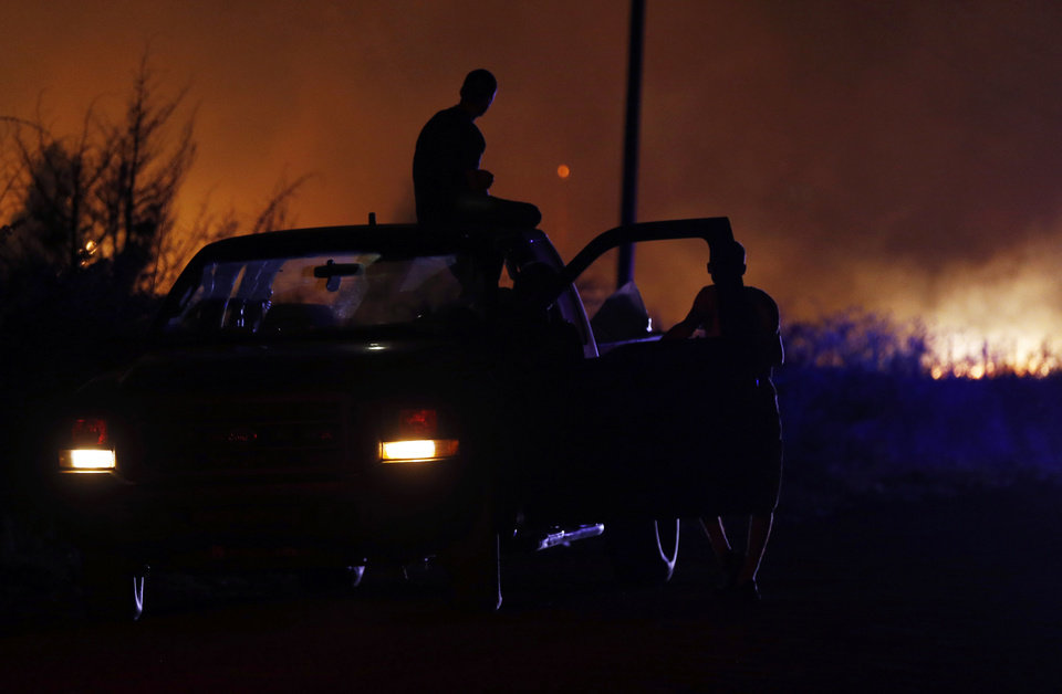 Photo - Residents evacuated from a mobile home park near Prairie Grove Rd. and Douglas are silhouetted by fire during wildfires in Logan County, Sunday, May 4, 2014. Photo by Nate Billings, The Oklahoman