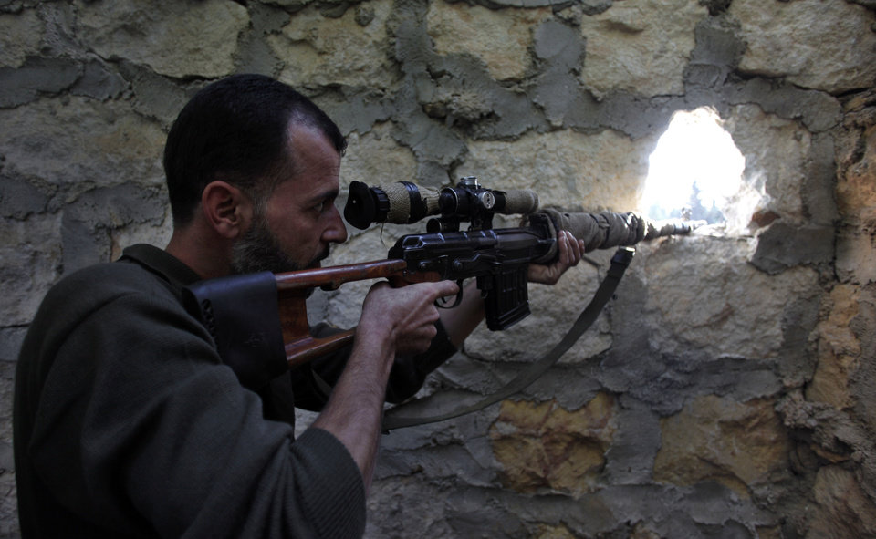 Photo - In this Wednesday, Nov. 14, 2012 file photo, a rebel sniper aims at a Syrian army position on the outskirts of Aleppo, Syria. Through mid-2012, rebel power grew and Assad's army ramped up its response. Relentless government shelling leveled neighborhoods and killed hundreds. Regular reports emerged of mass killings by the regime or thugs loyal to it, pushing more Syrians toward armed struggle. The government, which considers the opposition terrorist gangs backed by foreign powers, denied any role, and does not respond to requests for comment on its military. The rebels, too, were accused of atrocities. (AP Photo/ Khalil Hamra, File)