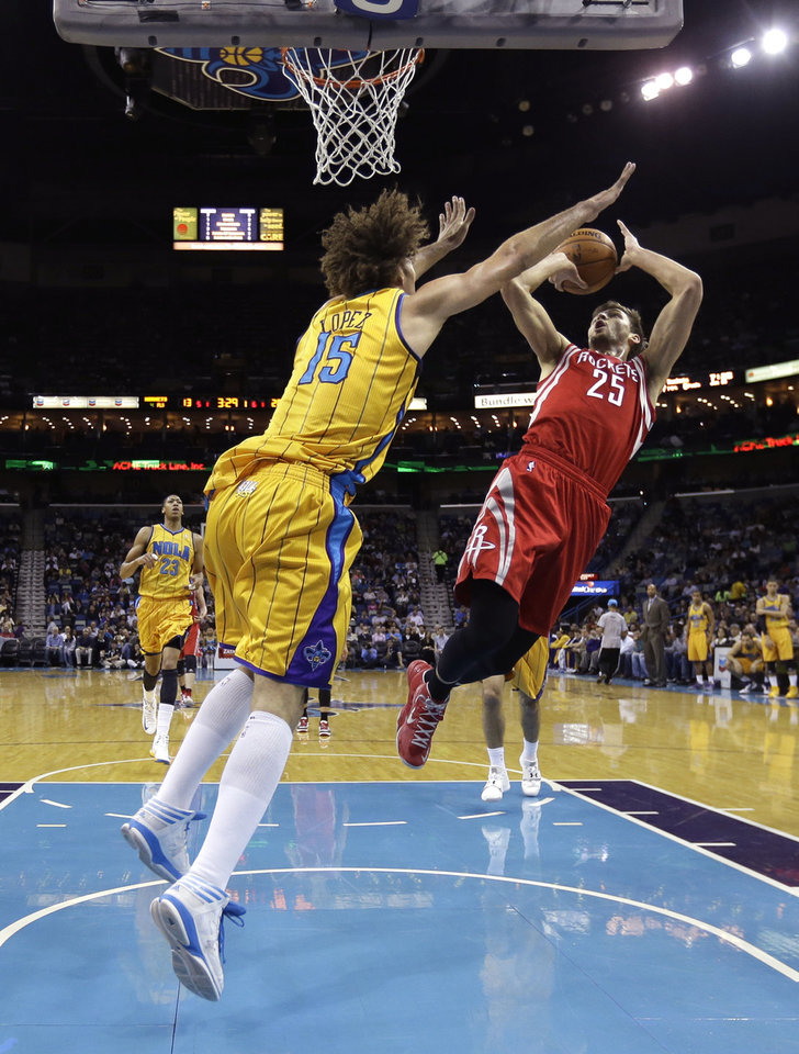 Photo - Houston Rockets small forward Chandler Parsons (25) shoots against New Orleans Hornets center Robin Lopez (15) in the first half of an NBA basketball game in New Orleans, Friday, Jan. 25, 2013. (AP Photo/Gerald Herbert)