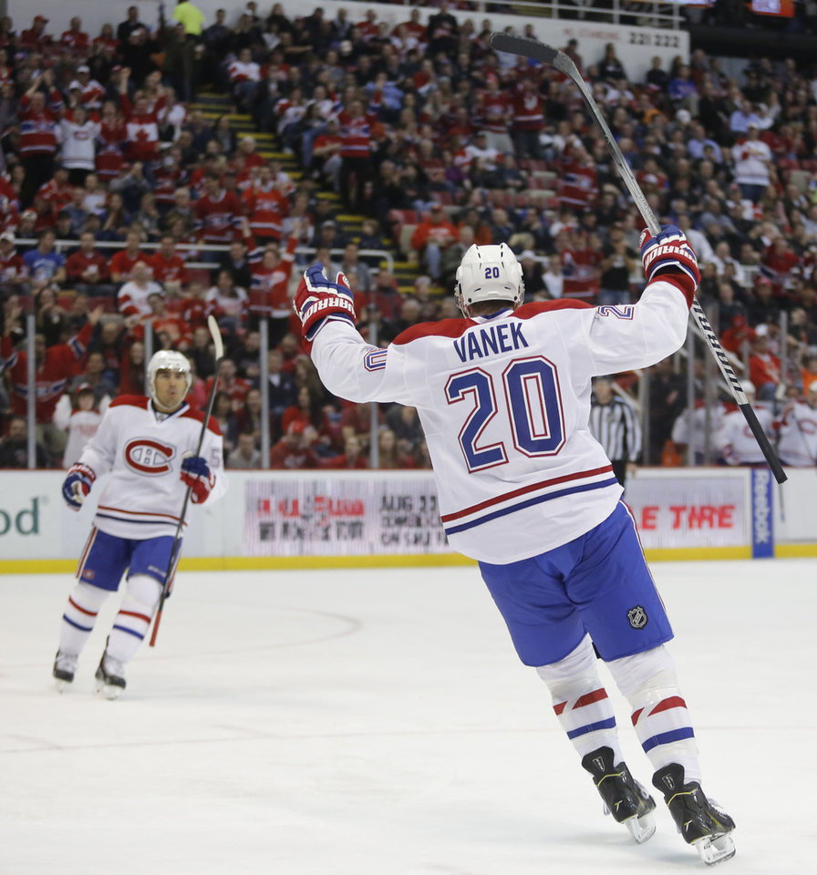 Photo - Montreal Canadiens' Thomas Vanek (20) of Austria, and teammate Francis Bouillon, left, celebrate a goal by David Desharnais during the second period of an NHL hockey game against the Detroit Red Wings Thursday, March 27, 2014, in Detroit. (AP Photo/Duane Burleson)