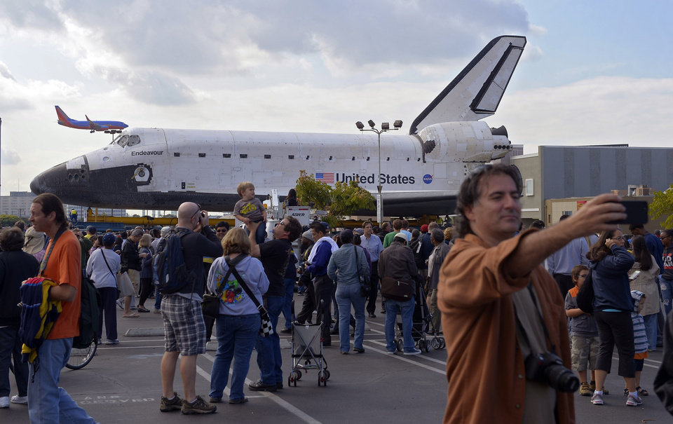 Photo -   Spectators gather around the Space Shuttle Endeavour before it is moved along city streets, Friday, Oct.12, 2012, in Los Angeles. Endeavour's two-day, 12-mile road trip to the California Science Center, where it will be put on display, kicked off early Friday. Rolled on a 160-wheeled carrier, it left from a hangar at the Los Angeles International Airport, passing diamond-shaped