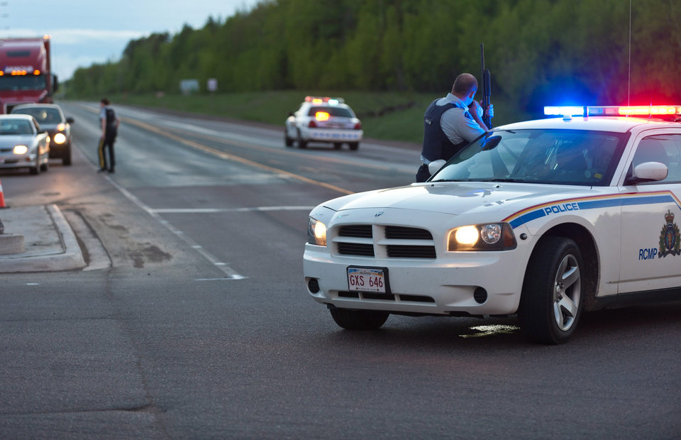 Photo - Royal Canadian Mounted Police officers use their vehicles to create a keep a perimeter in Moncton, New Brunswick on Wednesday June 4, 2014. The RCMP in New Brunswick said an undisclosed number of people have been shot and a manhunt is underway in the north end of Moncton for a man armed with guns.(AP Photo/The Canadian Press, Marc Grandmaison)