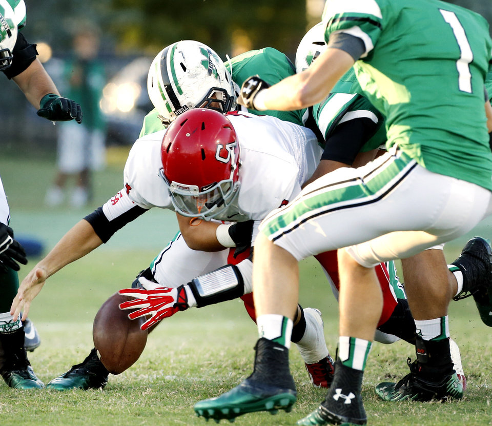 Photo - Titan quarterback Stevie Thompson fumbles on the first play from scrimmage as the Carl Albert Titans play the Bishop McGuinness Irish on Friday, Oct. 4, 2013 in Oklahoma City, Okla.  Thompson recovered the ball.  Photo by Steve Sisney, The Oklahoman
