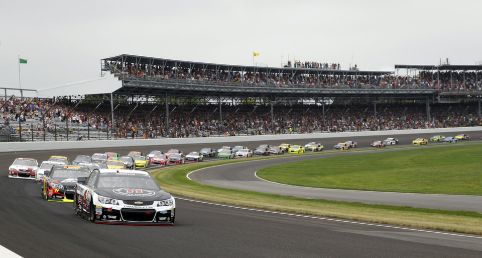 Photo - Kevin Harvick leads the field for the start of the Brickyard 400 auto race at Indianapolis Motor Speedway in Indianapolis, Sunday, July 27, 2014. (AP Photo/Tom Strattman)