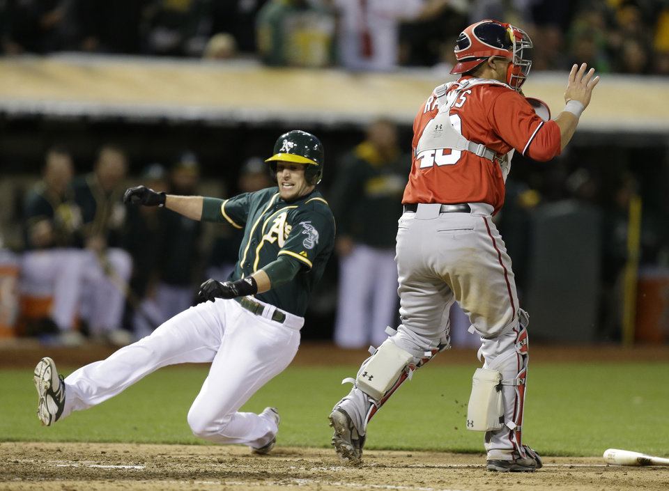 Photo - Oakland Athletics' Jed Lowrie, left, slides to score behind Washington Nationals catcher Wilson Ramos in the ninth inning of a baseball game Saturday, May 10, 2014, in Oakland, Calif. Lowrie scored on a single by Athletics' Josh Donaldson. (AP Photo/Ben Margot)