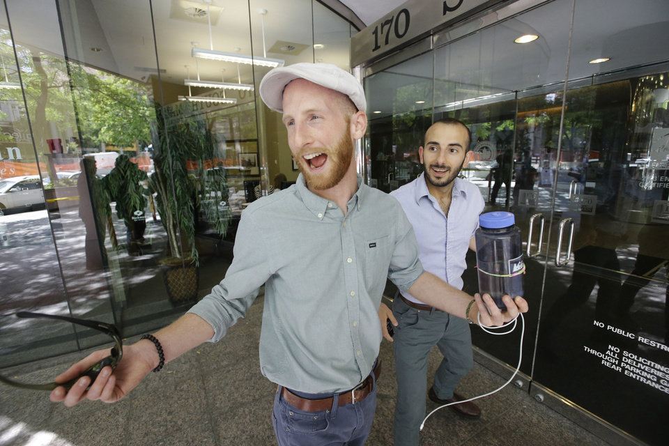 Photo - Plaintiffs Derek Kitchen, left, and his partner, Moudi Sbeity, one of three couples who brought a lawsuit against Utah's gay marriage ban, celebrate as they arrive at their lawyer's office in Salt Lake City on Wednesday, June 25, 2014. A federal appeals court on Wednesday ruled for the first time that states must allow gay couples to marry, finding the Constitution protects same-sex relationships and putting a remarkable legal winning streak across the country one step closer to the U.S. Supreme Court. (AP Photo/Rick Bowmer)