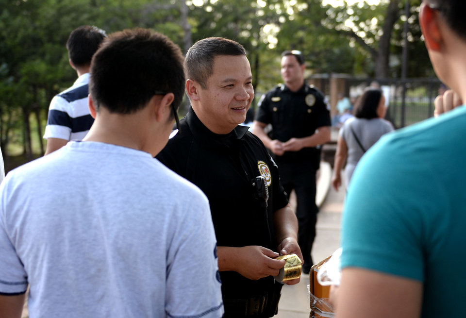 Photo -  Oklahoma County sheriff's deputy Tom Ly hands out stickers to patrons of the Moon Festival in September at Will Rogers Park in Oklahoma City. [Photo by Jackie Dobson, For The Oklahoman]