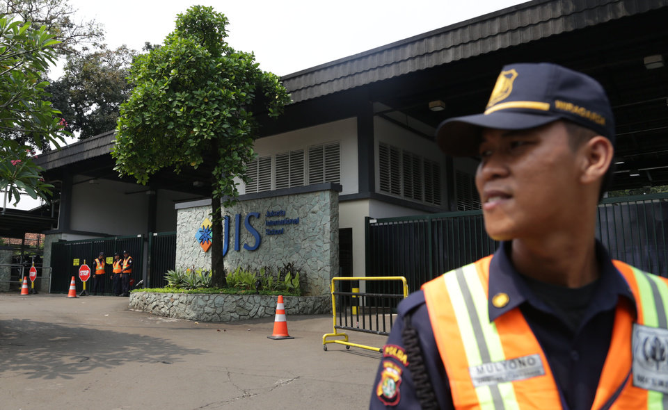 Photo - In this Thursday, May 8, 2014 photo, a security guard stands at the entrance of Jakarta International School (JIS) compound in Jakarta, Indonesia. U.S. citizen William Vahey taught here from 1992-2002. Vahey began his international teaching career with a series of stays around the Middle East and Europe, and by 1992, Vahey and his wife moved to Indonesia. He was one of the most beloved teachers in the world of international schools that serve the children of diplomats, well-off Americans and local elites. That was the public persona of William Vahey until a maid stole a memory drive from him in November. On it was evidence that Vahey molested scores of adolescent boys, possibly more. (AP Photo/Achmad Ibrahim)