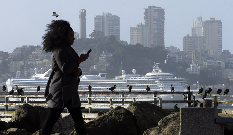 Photo - A woman walks on a shoreline path with a view of the San Francisco skyline and a cruise ship Thursday, Dec. 10, 2015, as seen from Treasure Island in San Francisco Bay. Another storm system is expected this afternoon, bringing rain to the Bay Area. (AP Photo/Ben Margot)