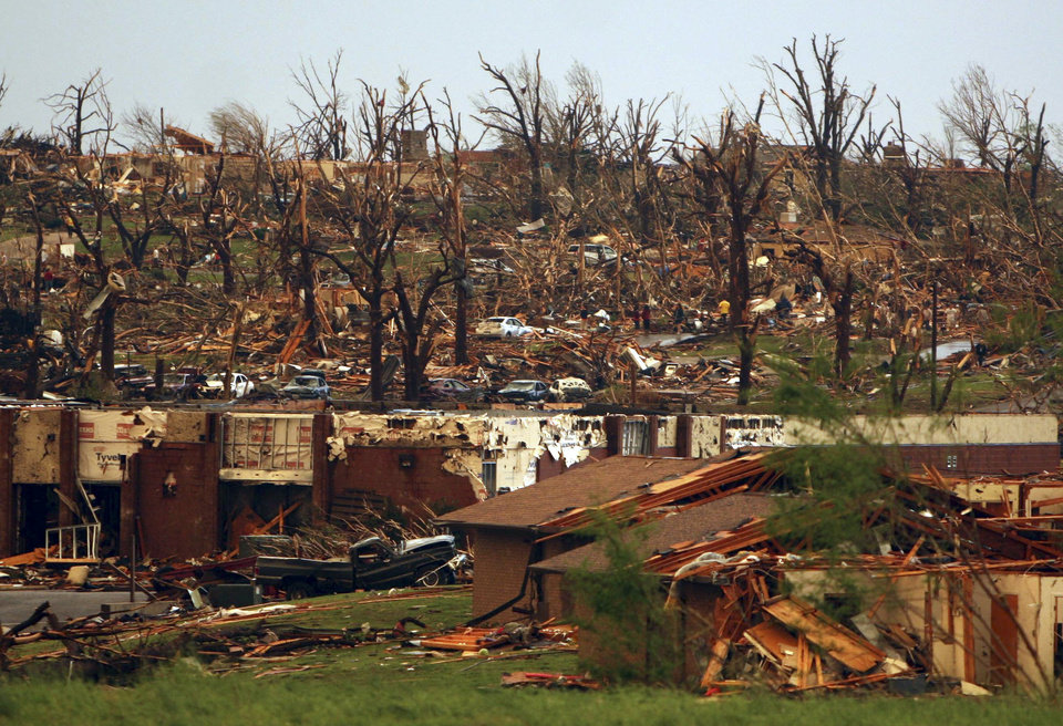 Photo - Rescuers and neighbors look through the the wreckage of destroyed homes on a hillside in Joplin, Mo., Sunday, May 22, 2011. A large tornado moved through much of the city, damaging a hospital and hundreds of homes and businesses. (AP Photo/Mark Schiefelbein) ORG XMIT: MOMS105