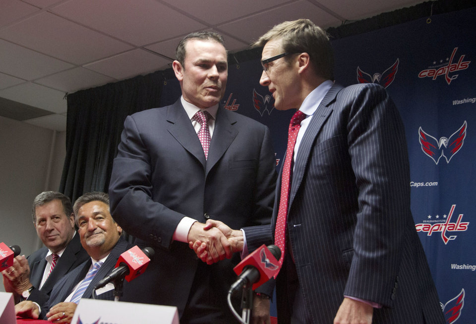 Photo -   Washington Capitals coach Adam Oates, standing left, and general manager George McPhee, shake hands during a news conference introducing the NHL hockey team's new coach in Washington, Wednesday, June 27, 2012. At left are team president Dick Patrick, seated left, and owner Ted Leonsis. (AP Photo/Manuel Balce Ceneta)