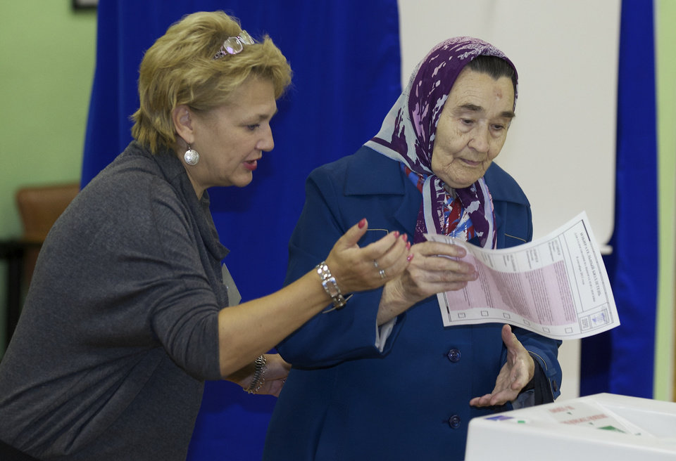 Photo - A member of the election commission, left, helps a woman to cast her ballot at a polling station in Moscow, Russia, Sunday, Sept. 8, 2013. Moscow is holding its first mayoral election in a decade. Although an incumbent backed by President Vladimir Putin is expected to win Sunday's election handily, the candidacy of charismatic opposition leader Alexei Navalny is changing Russian politics in ways that could pose a risk for the Kremlin in the months and years ahead. (AP Photo/Alexander Zemlianichenko)