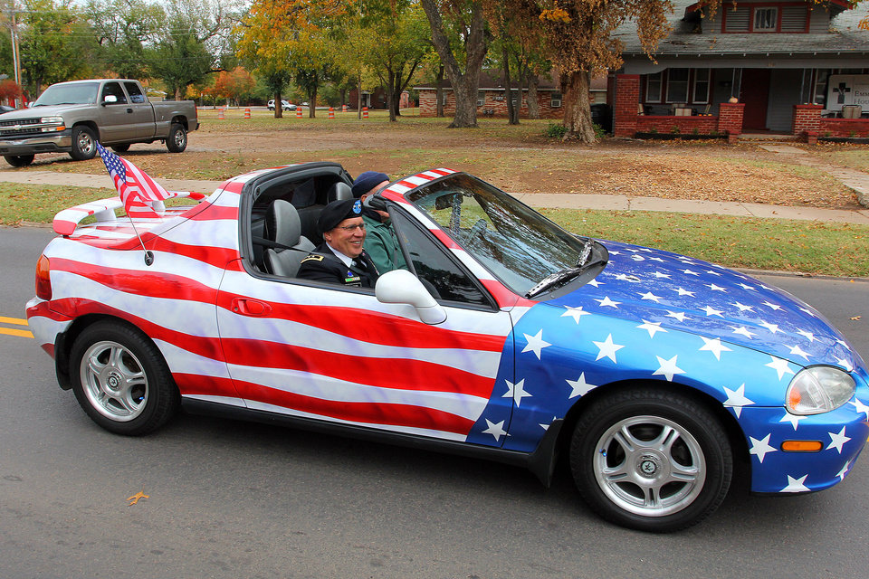 Major General Myles Deering, Adjutant General of Oklahoma rides in a car decorated with the Stars and Stripes during the Veterans Day parade in Norman Sunday. PHOTO BY HUGH SCOTT FOR THE OKLAHOMAN ORG XMIT: KOD