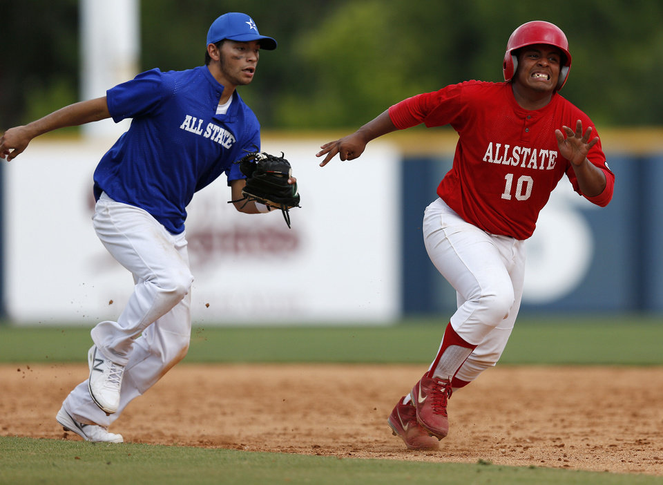 Photo - Leno Ramirez, of Dover, runs from Cade Clay, of Rattan, during the small school All-State Baseball game between East and West at Johnson Stadium at Oral Roberts University in Tulsa, Okla., Tuesday, July 30, 2013. GARETT FISBECK/Tulsa World