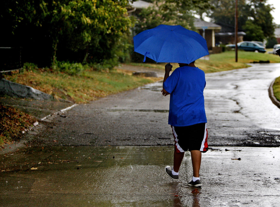 A person stays dry under an umbrella as they walk down a street in The Village, Okla., after a storm, Saturday, August 18, 2012. Photo by Bryan Terry, The Oklahoman