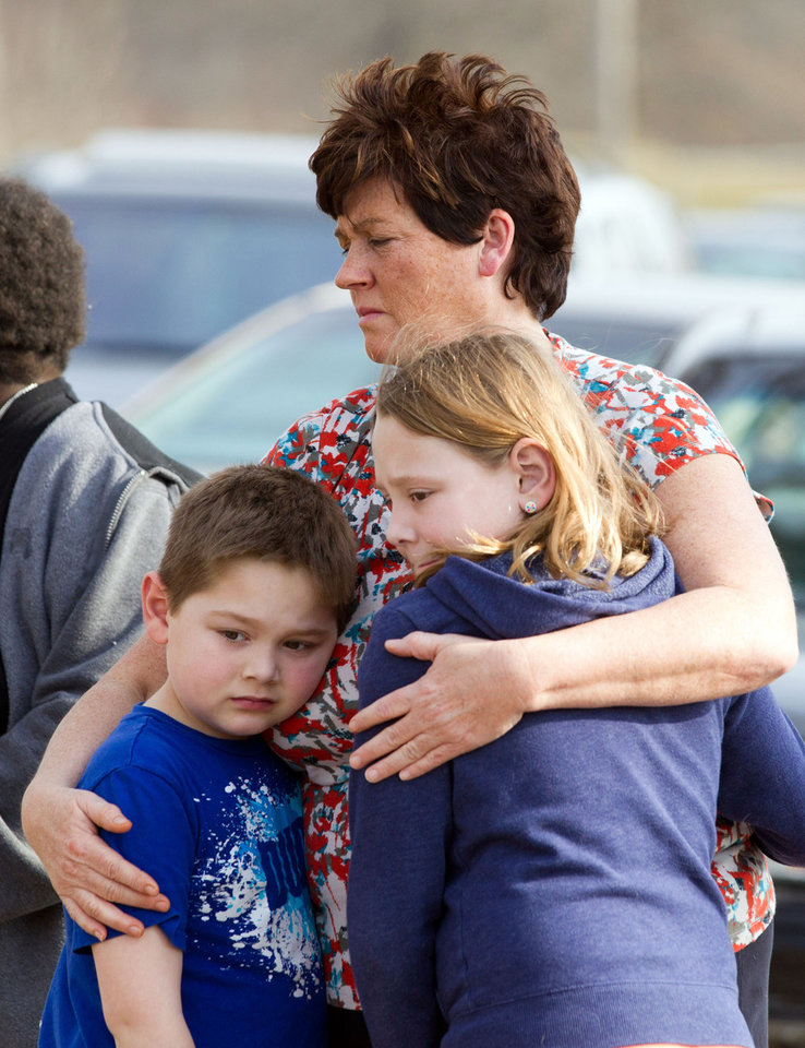 Photo - An unidentified woman and her children visit the crash site that claimed the lives of six teens early in the morning on Park Ave. in Warren, Ohio on Sunday, March 10, 2013. (AP Photo/Scott R. Galvin)
