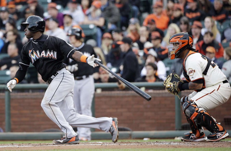Photo - Miami Marlins' Adeiny Hechavarria drives in a run with a single against the San Francisco Giants during the second inning of a baseball game on Saturday, May 17, 2014, in San Francisco. (AP Photo/Marcio Jose Sanchez)