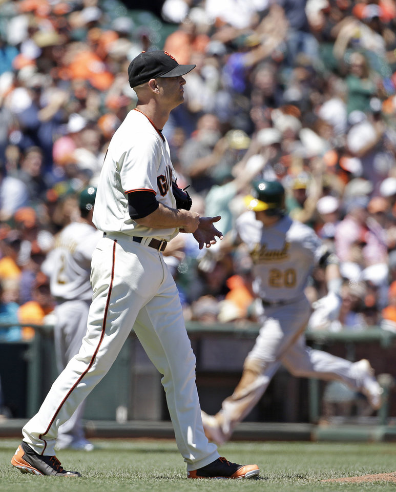 Photo - San Francisco Giants starting pitcher Tim Hudson, left, walks back to the mound after giving up a two run homer to the Oakland Athletics' Josh Donaldson, right, in the sixth inning of their interleague baseball game Thursday, July 10, 2014, in San Francisco. (AP Photo/Eric Risberg)