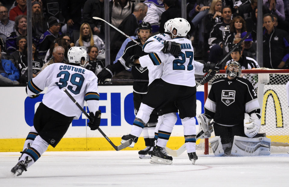 Photo - San Jose Sharks center Patrick Marleau, center, celebrates his game-winning goal with defenseman Scott Hannan, second from right, as Los Angeles Kings goalie Jonathan Quick, right, looks on and center Logan Couture skates in during the overtime period in Game 3 of an NHL hockey first-round playoff series, Tuesday, April 22, 2014, in Los Angeles. The Sharks won 4-3. (AP Photo/Mark J. Terrill)