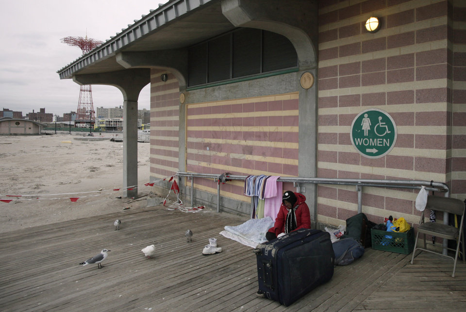 Photo - CORRECTS DATE TO NOV. 7, INSTEAD OF NOV. 9 - A homeless woman sits on the Coney Island boardwalk, Wednesday, Nov. 7, 2012 in New York. Residents of New York and New Jersey who were flooded out by Superstorm Sandy waited with dread Wednesday and heard warnings to evacuate for the second time in two weeks as another, weaker storm spun toward them and threatened to inundate their homes again or simply leave them shivering in the dark for even longer. (AP Photo/Mark Lennihan) ORG XMIT: NYML103