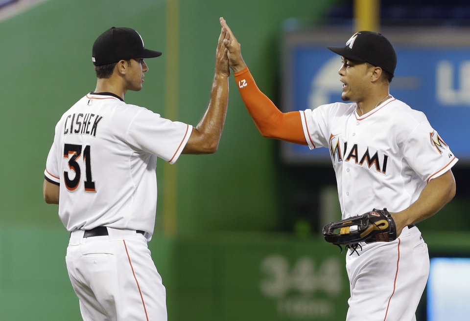 Photo - Miami Marlins' closer Steve Cishek (31) and right fielder Giancarlo Stanton, right, celebrate an 8-5 victory over the Colorado Rockies in a baseball game on Thursday, April 3, 2014, in Miami. (AP Photo/Lynne Sladky)