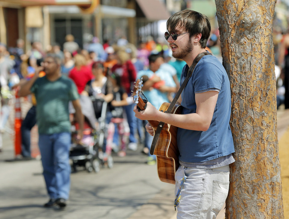Photo - Ethan Schlecht, who performs as Feline Valentine, plays his guitar as people walk on NW 23 during the Open Streets OKC event. From noon until 4 p.m. Sunday, NW 23 between Robinson and Western was closed to vehicles for the event.  NATE BILLINGS