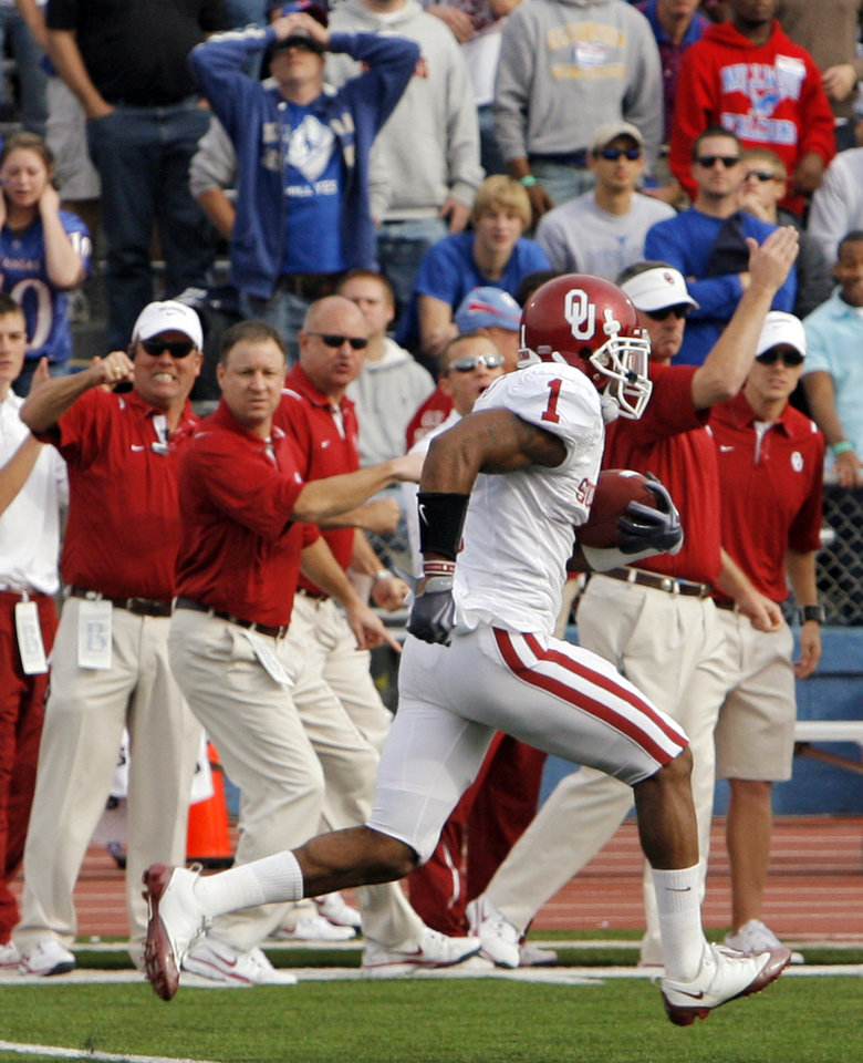Photo - OU's Dominique Franks (1) returns an interception for a touchdown as OU staff and KU fans react in the second quarter of the college football game between the University of Oklahoma Sooners (OU) and the University of Kansas Jayhawks (KU) on Saturday, Oct. 24, 2009, in Lawrence, Kan. OU won, 35-13. Photo by Nate Billings, The Oklahoman