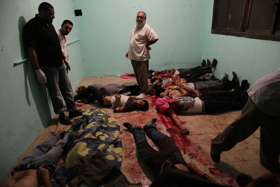 Photo - EDITOR'S NOTE: GRAPHIC CONTENT - Bodies lie in a room of a hospital after shooting happened at the Republican Guard building in Nasser City, Cairo, Monday, July 8, 2013. Egyptian soldiers and police opened fire on supporters of the ousted president early Monday in violence outside the military building in Cairo where demonstrators had been holding a sit-in, government officials and witnesses said. (AP Photo/Wissam Nassar)
