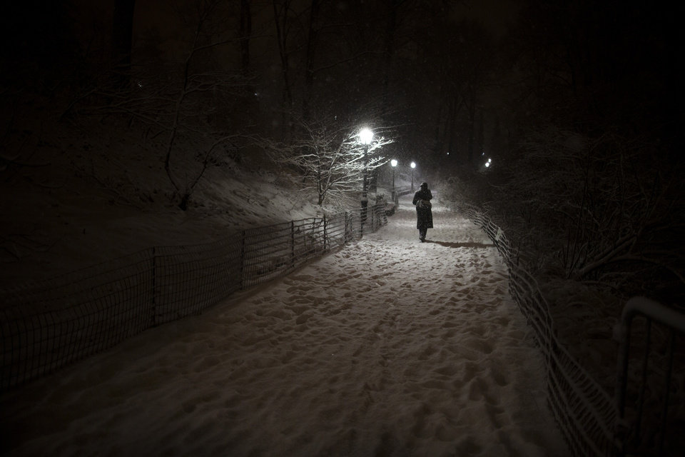 Photo - A pedestrian walks along a snowy path in Central Park, Friday, Feb. 8, 2013, in New York. Snow began falling across the Northeast on Friday, ushering in what was predicted to be a huge, possibly historic blizzard and sending residents scurrying to stock up on food and gas up their cars. (AP Photo/John Minchillo)