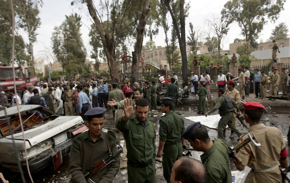 Photo -   Yemeni officials and police gather at the site of a car bomb attack targeting the motorcade of the country's defense minister in Sanaa, Yemen, Tuesday, Sept. 11, 2012. Yemeni officials say a car bomb targeting the motorcade of the country's defense minister has killed several people, but the minister escaped unharmed. (AP Photo/Hani Mohammed)