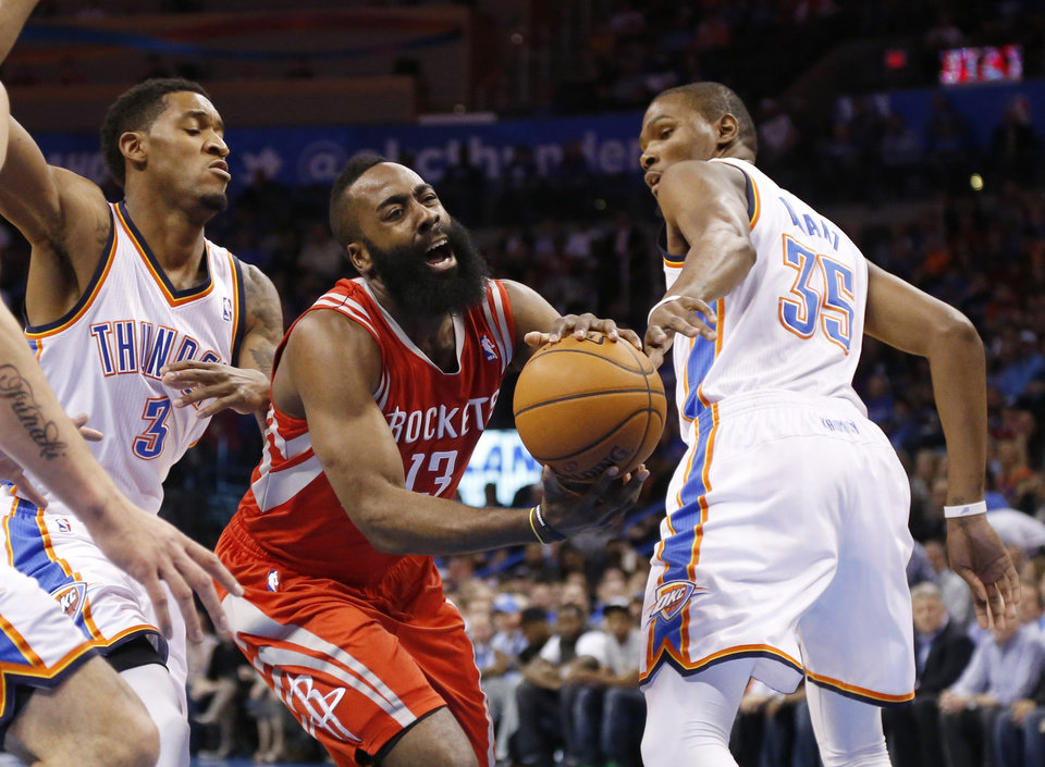 Photo - Houston Rockets guard James Harden (13) drives between Oklahoma City Thunder forward Perry Jones (3) and forward Kevin Durant (35) during the first quarter of an NBA basketball game in Oklahoma City, Tuesday, March 11, 2014. (AP Photo/Sue Ogrocki)