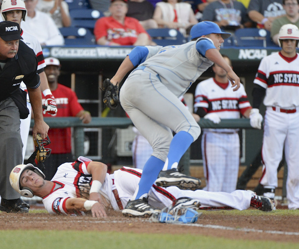 Photo - UCLA pitcher Nick Vander Tuig steps over North Carolina State's Jake Armstrong after tagging him out at home plate on a single by Trea Turner in the third inning of an NCAA College World Series game in Omaha, Neb., Tuesday, June 18, 2013. (AP Photo/Ted Kirk)