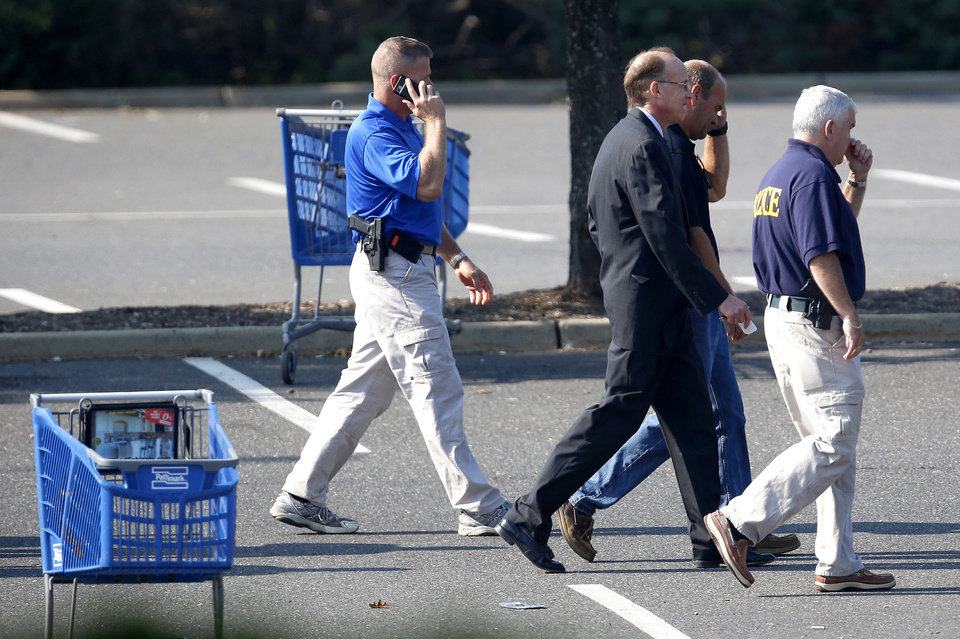 Photo -   Middlesex County prosecutor Bruce Kaplan, center, walks with officials on the parking lot of a Pathmark grocery store where three people died in an early morning shooting in Old Bridge, N.J., Friday, Aug. 31, 2012. Officials say a supermarket employee killed two people at the store early Friday and then fatally shot himself. Authorities say he opened fire on employees he saw when he walked into the Pathmark store. The store's front windows were shattered by gunfire. The motive is being investigated. (AP Photo/Julio Cortez)