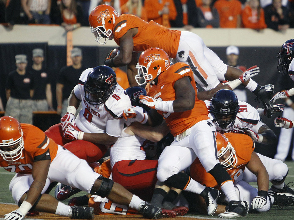 Photo -   Oklahoma State running back Joseph Randle, top, goes up and over a pile of players to score in the third quarter of an NCAA college football game against Texas Tech in Stillwater, Okla., Saturday, Nov. 17, 2012. Oklahoma State won 59-21. (AP Photo/Sue Ogrocki)