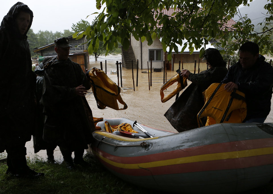 Photo - Bosnian Army prepare to rescue a woman from a house near Zepce, 120 kms north of Sarajevo, Thursday May 15, 2014. Heavy rainfall caused the river Bosna to flood surrounding areas causing power cuts and road blockades in some suburban and rural areas. (AP Photo/Amel Emric)