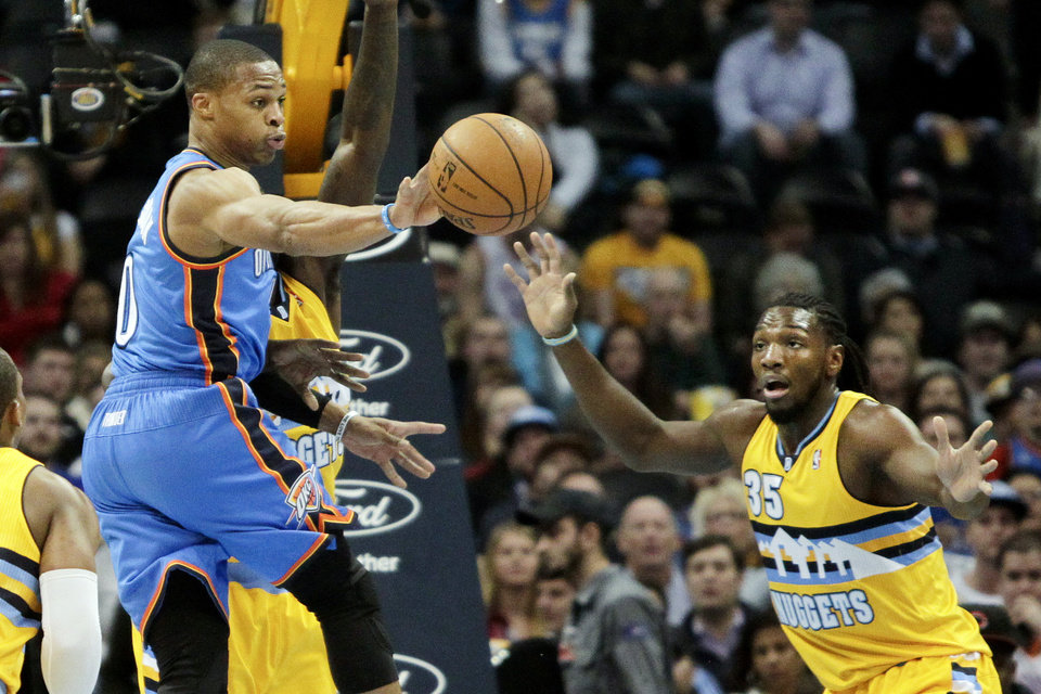 Oklahoma City Thunder's Russell Westbrook, left, make a pass with Denver Nuggets' Kenneth Faried, right, covering during the first quarter of an NBA basketball game Tuesday, Dec. 17, 2013, in Denver. (AP Photo/Barry Gutierrez)