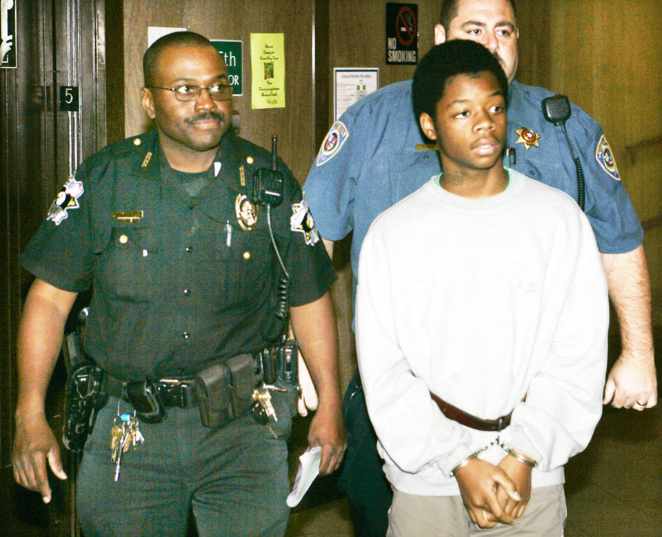 Photo - Jevontai Ingram, 15, walks to court Friday to testify against two men he alleges forced him to do a robbery. PHOTO BY Steve Gooch, The Oklahoman