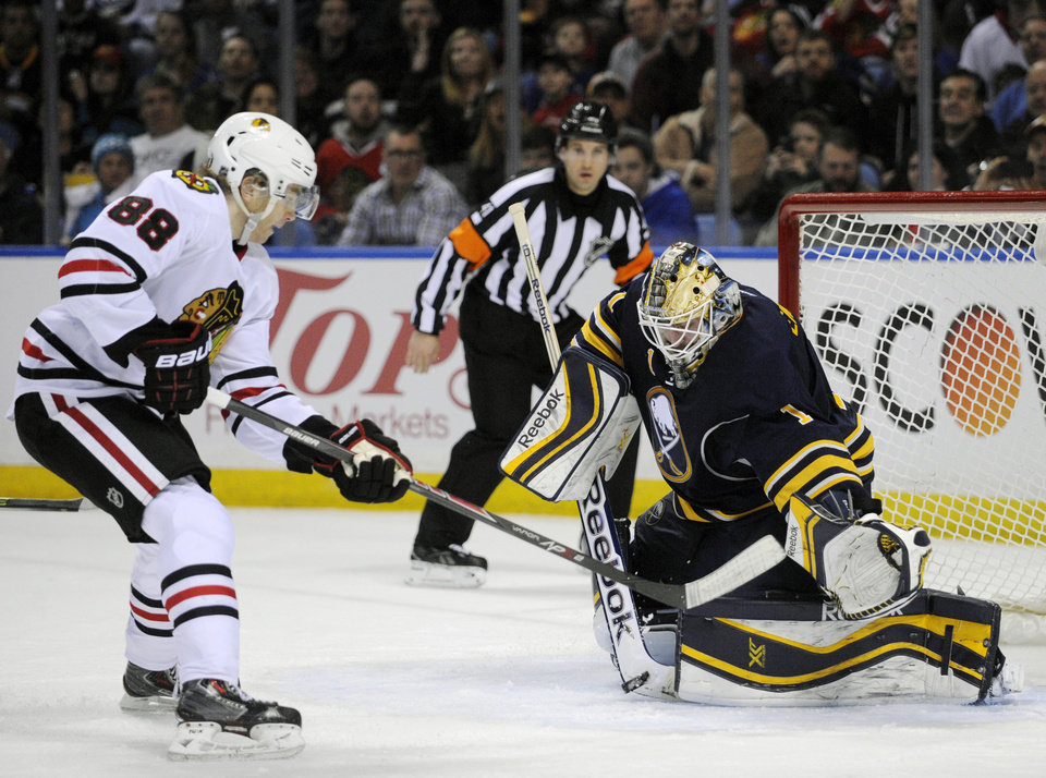 Photo - Chicago Black Hawks right winger Patrick Kane (88) gets stopped on a breakaway by Buffalo Sabres goaltender Jhonas Enroth (1), of Sweden, during the second period of an NHL hockey game in Buffalo, N.Y., Sunday, March 9,  2014. (AP Photo/Gary Wiepert)