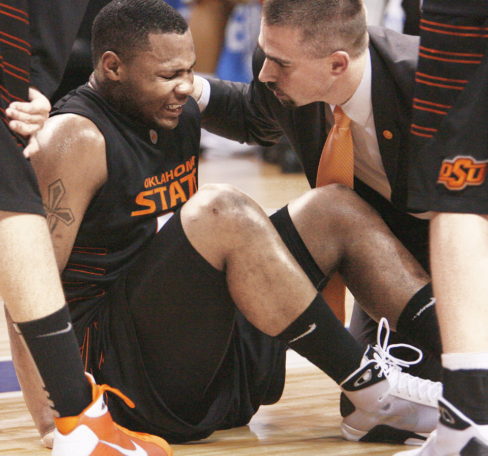Photo - Oklahoma State's Byron Eaton sits on the court in pain after injuring his foot against Missouri in the first half Friday at the Ford Center.  Photo by chris landsberger, the oklahoman