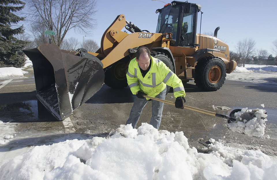 Photo - Supervisor of Streets Jim Veugeler clears snow from a storm drain as maintenance worker Dave Shine operates a front end loader in Crystal Lake, Ill., Wednesday, Feb 18, 2014. Weeks of subfreezing weather are giving way, at least briefly, to temperatures in the 50s, putting cities on guard for flooding, roof collapses and clogged storm drains. A new system is expected to arrive late Wednesday night that could include rain, freezing rain, snow, thunder, sleet, ice and 50 mph wind gusts. (AP Photo/Northwest Herald, H. Rick Bamman)  MANDATORY CREDIT