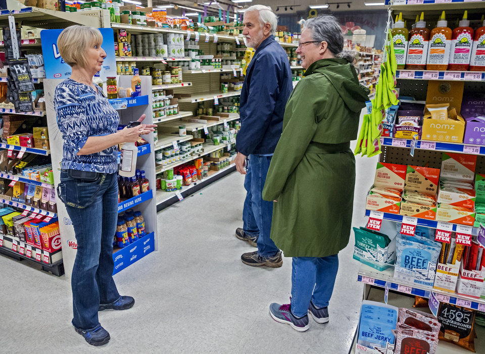 Photo - Assistant manager Betty Black, left, talks with customers Terry and Lynda Witty as they shop for items at the Homeland grocery store located at 2400 S. Cornwell in Yukon, Okla. on Thursday, March 19, 2020. Homeland has dedicated the first hour of store operations to senior customers and those who have medical conditions that put them at risk from COVID-19.  [Chris Landsberger/The Oklahoman]