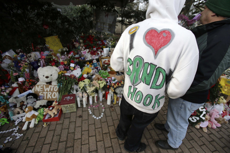 Photo - A Sandy Hook resident wears a handmade sweatshirt in support of his town while looking at a memorial to the Newtown shooting victims in the Sandy Hook village of Newtown, Conn., Saturday, Dec. 22, 2012.  The funerals for the victims of the school shooting are wrapping up after a wrenching week of farewells. Twenty children and six adults were killed at Sandy Hook Elementary School on Dec. 14.  Adam Lanza, the lone gunman, killed his mother before going on the rampage and then committed suicide. (AP Photo/Seth Wenig) ORG XMIT: CTSW106