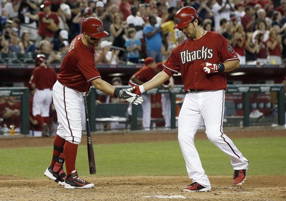Photo - Arizona Diamondbacks' Eric Chavez, right, shakes hands with teammate Cody Ross as Chavez reaches home plate after hitting a 2-run home run against the Los Angeles Dodgers during the fifth inning of a baseball game on Sunday, May 18, 2014, in Phoenix. (AP Photo/Ross D. Franklin)