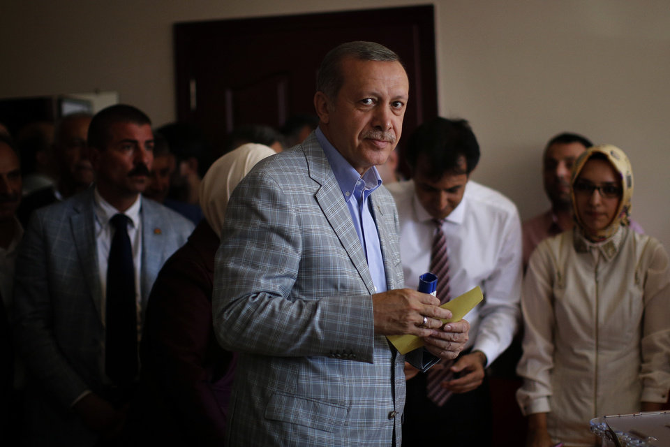 Photo - Prime Minister Recep Tayyip Erdogan, who is the front-runner in Turkey's presidential election, holds his ballot paper at a polling station in Istanbul, Turkey, Sunday, Aug. 10, 2014. Turks were voting in their first direct presidential election Sunday - a watershed event in Turkey's 91-year history, where the president was previously elected by Parliament. Prime Minister RecepTayyip Erdogan, who has dominated the country's politics for the past decade, is the strong front-runner to replace the incumbent, Abdullah Gul, for a five-year term. (AP Photo/Emilio Morenatti)